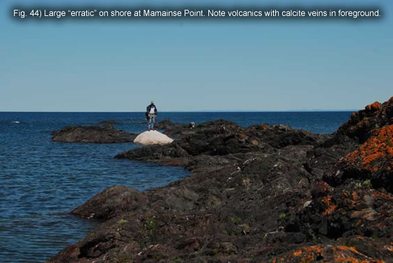 "Fig. 44) Large ""erratic"" on shore at Mamainse Point. Note volcanics with calcite veins in foreground."